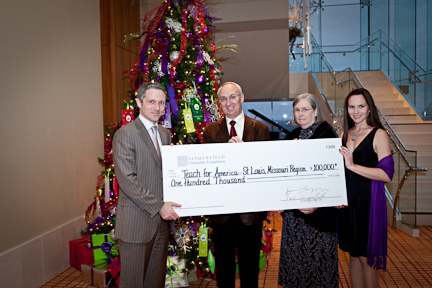 Scott Baier (left), executive director of Teach For American-St. Louis, accepts a ceremonial check from Rex and Jeanne Sinquefield, and their daughter, Katie (right).