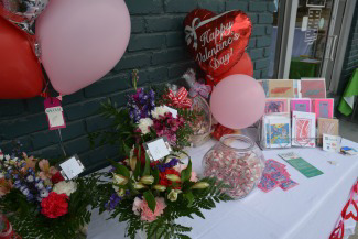 Table decorated with flowers and Valentine's Day balloons.
