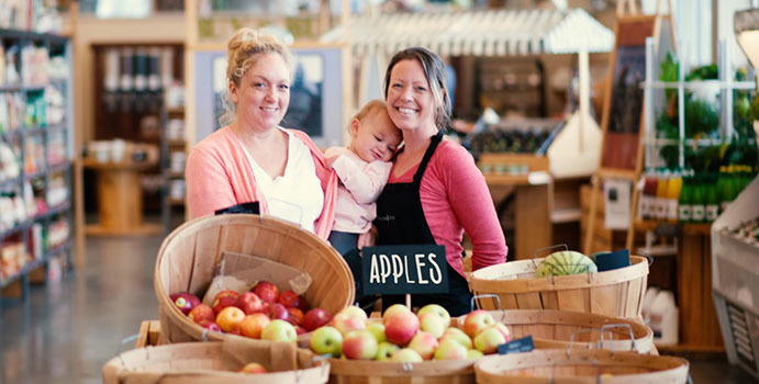 Two women holding a baby stand behind six barrels of apples