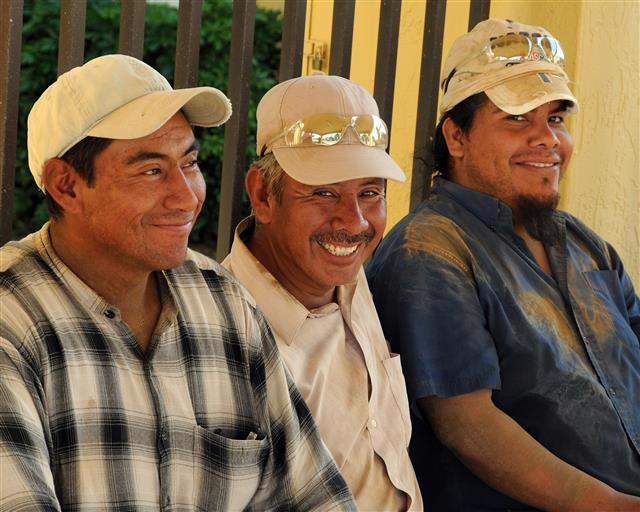 Three men wearing beige hats smile at the camera