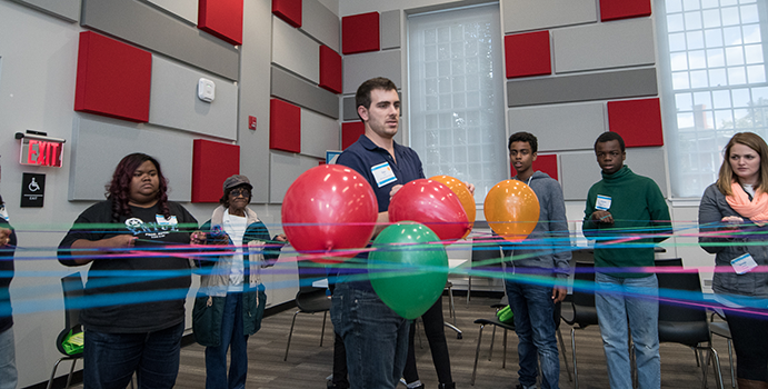 A teacher stands behind a balloon display in a room full of kids