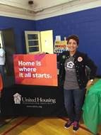 A woman wearing a black jean jacket stands next to a table with a sign that says: Home is where it all starts