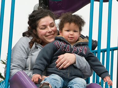 A mother and child sitting on top of a slide.