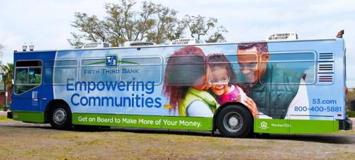 "A bus painted with a logo that says ""empowering communities"" and shows a picture of a family."