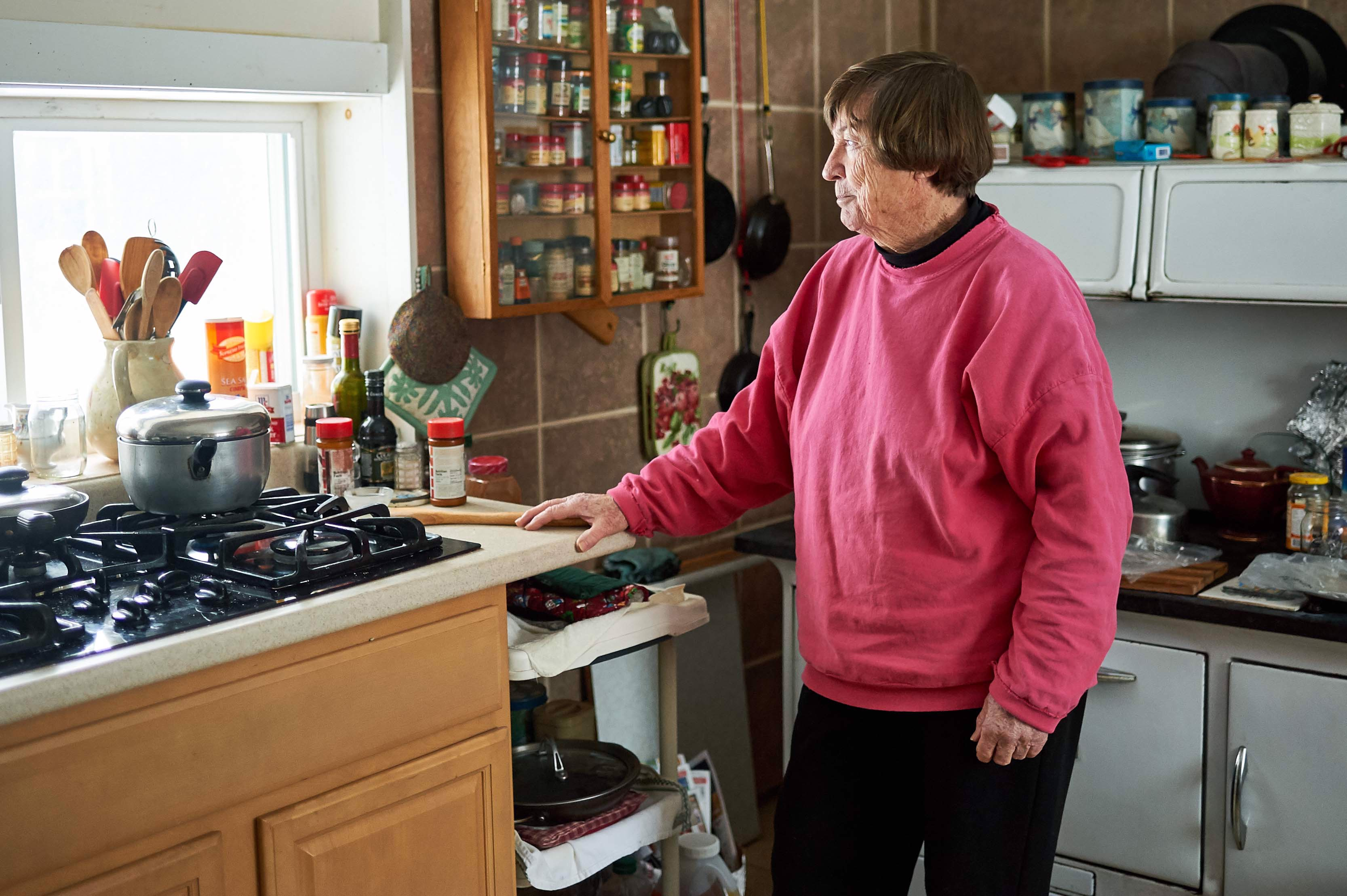 An elderly woman wearing a pink sweatshirt stands in her kitchen, staring out the window