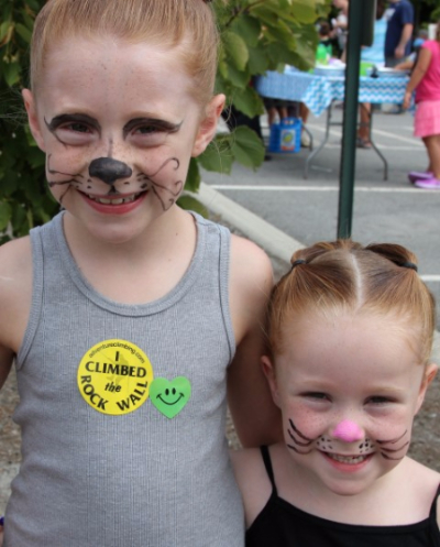Two little girls have their faces painted like cats