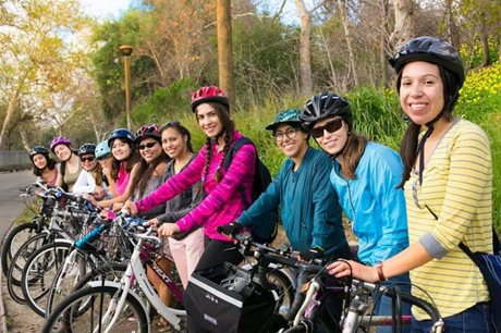 Several women are on their bikes next to a wooded area