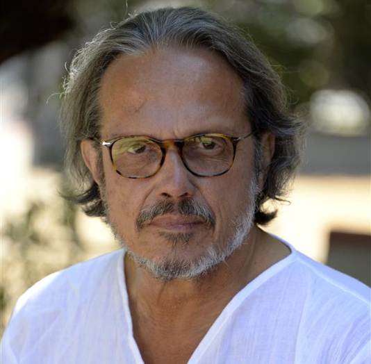 A man with a goatee wearing glasses and a white shirt