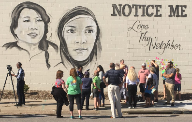 "A mural on a slate wall with two women's faces and the words ""Notice Me - Love Thy Neighbor"""