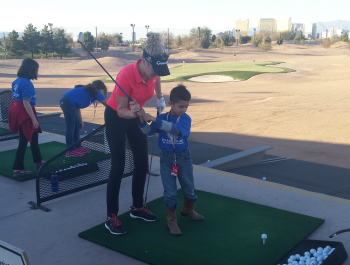 Instructor helps a child golf