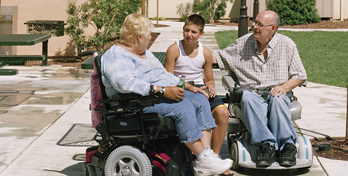 Two wheelchair users talk with a young boy on a bench