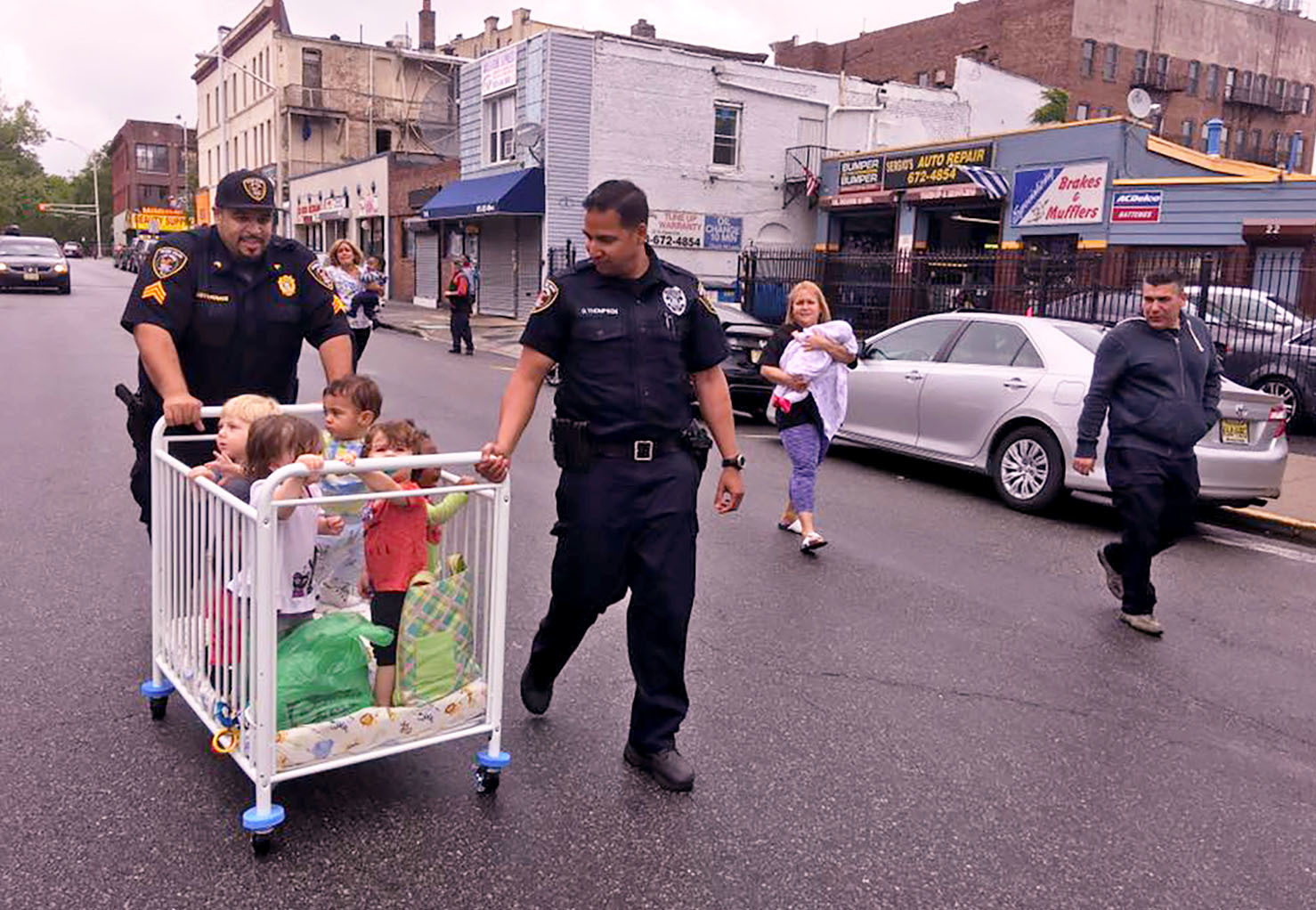 Two police officers walking with children in a crib on wheels