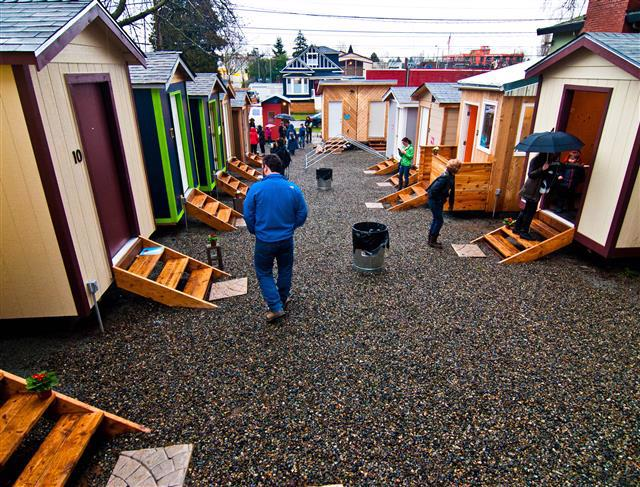 Man walks through a village of tiny homes
