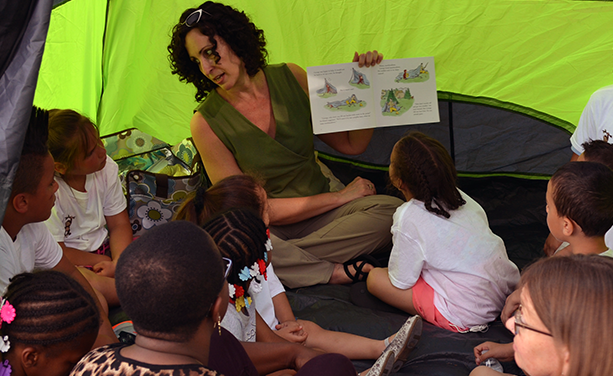 A woman holds up a book to give a theatrical performance to a mixed group of children in a green tent