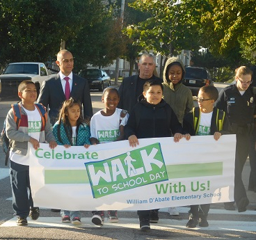 "A mixed group of students hold a ""Celebrate Walk to School Day With Us"" banner and are accompanied by a group of adults"
