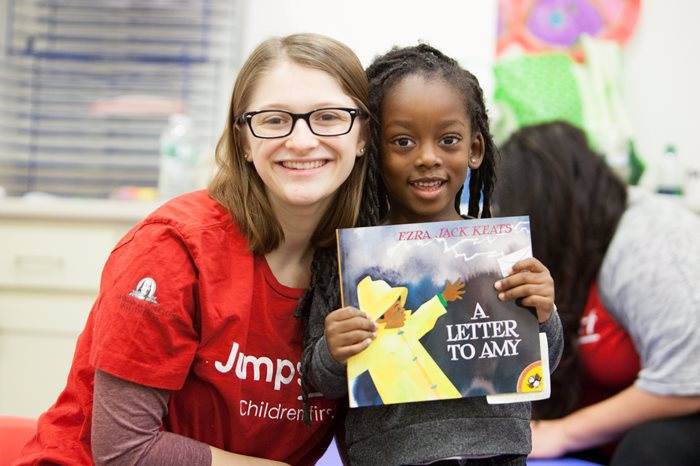 "A white teacher stands next to a black student who holds up a book titled ""A letter to Amy"""