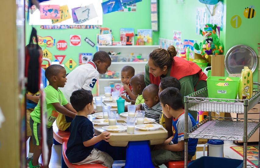 A teacher feeds a mixed group of children lunch