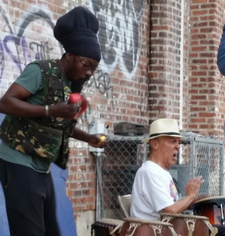 Two musicians play the congos in front of a brick building