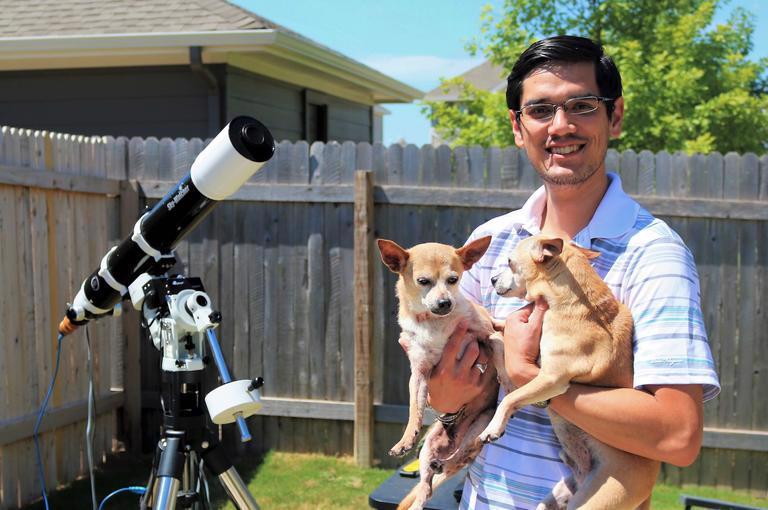 man holding two dogs next to a telescope