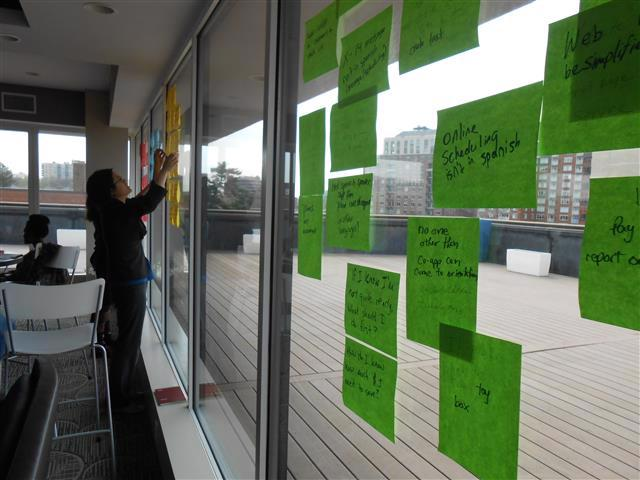 A woman hangs yellow sticky notes to a window