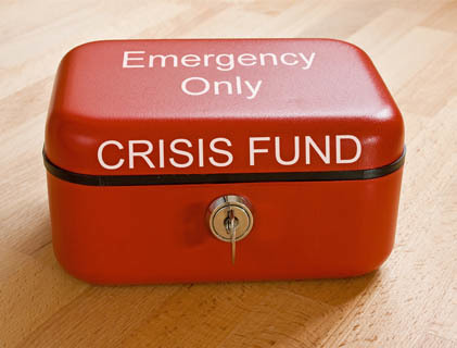 Lock box on a wooden table with white text that reads: Emergency Only Crisis Fund
