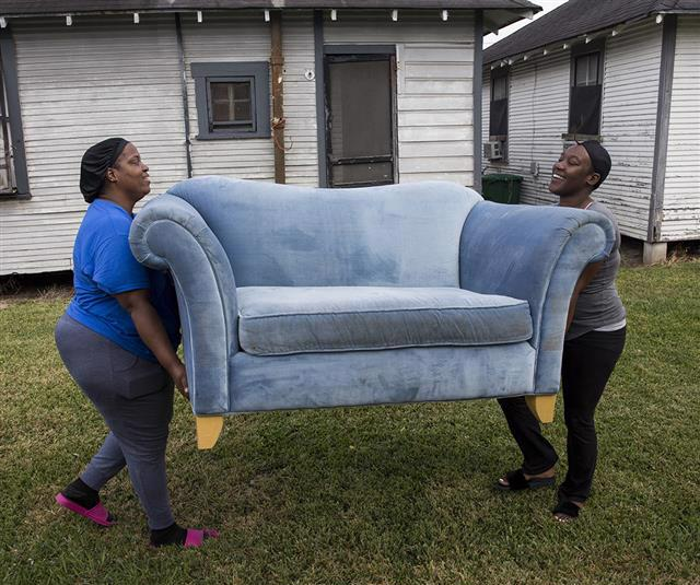 Two people carry a blue couch across a yard