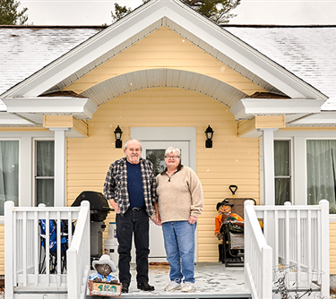 Two people stand in front of a yellow house with a white porch