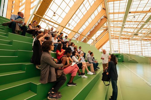 A mixed group of people sit on green bleachers in a large auditorium with wooden beams