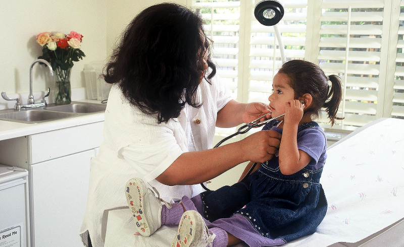 A nurse holds a stethoscope to a young girl's ears