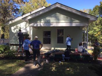 A group of men stand around a house that's slated for repairs