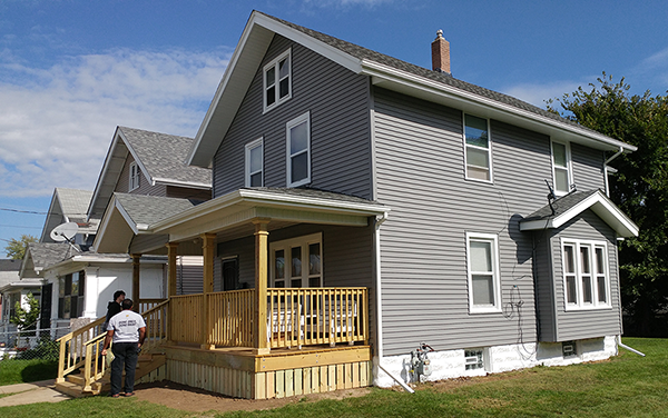 Newly-revitalized home with gray siding, white trim, and a porch under construction