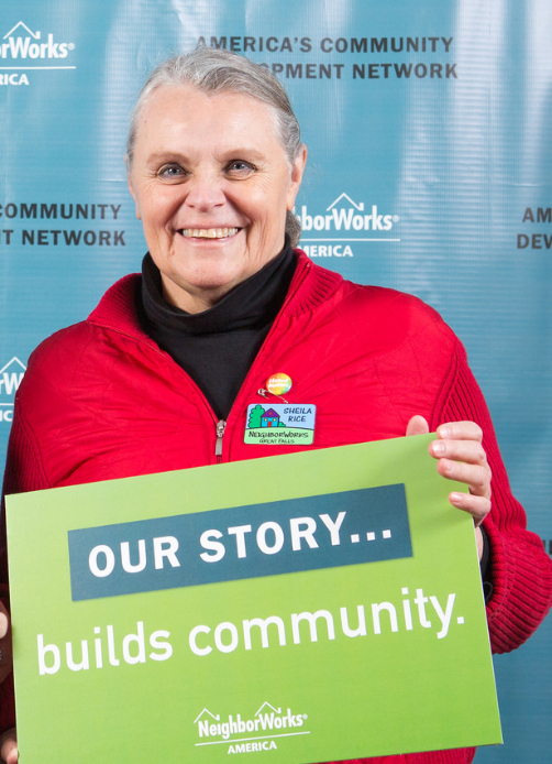 """Sheila Rice, wearing a red jacket, holds up a sign that says """"Our story builds community."""""""