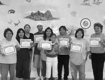 Native American men and women hold up certificates