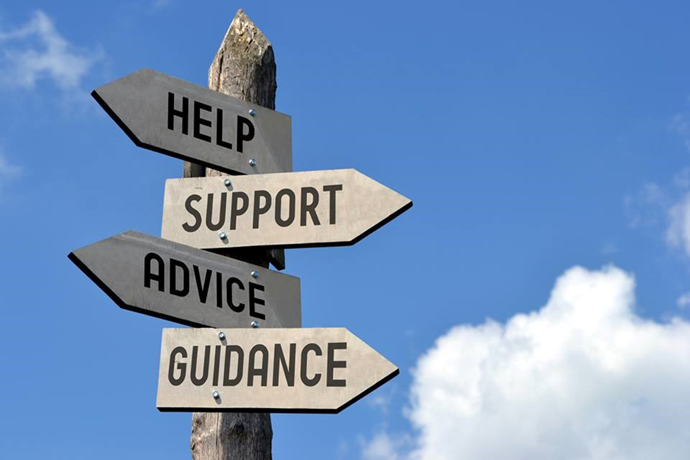 """Sign post with arrows pointing in different directions that read """"Help, Support, Advice, Guidance."""""""