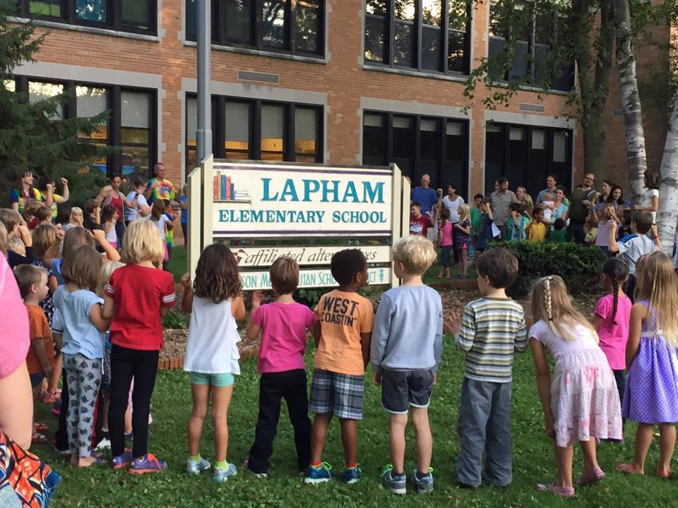 students in front of Lapham elementary school sign