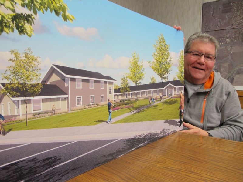 Image of Buster Langowski holding large photo of new housing complex